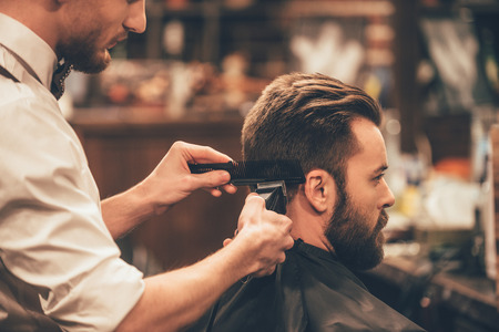 hair part: Professional styling. Close up side view of young bearded man getting haircut by hairdresser with electric razor at barbershop