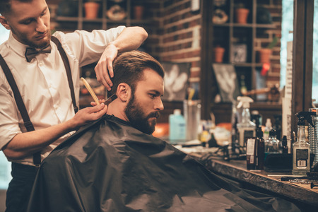 cutting hair: Making hair look magical. Young bearded man getting haircut with straight edge razor by hairdresser while sitting in chair at barbershop Stock Photo