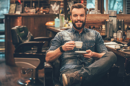 sitting small: Cup of fresh coffee at barbershop. Cheerful young bearded man looking at camera and holding coffee cup while sitting in chair at barbershop Stock Photo