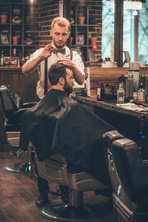Kapper op het werk. Volledige lengte van de jonge man met een baard die kapsel krijgt door kapper tijdens de vergadering in de stoel bij kapperszaak