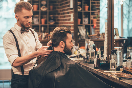 barber shop: Perfect trim at barbershop. Young bearded man getting haircut by hairdresser with electric razor while sitting in chair at barbershop