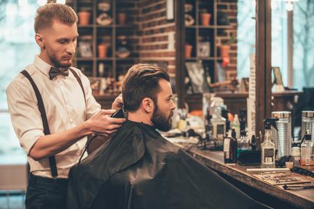 Perfekte Besatz an Friseurladen. Junger bärtiger Mann Frisur mit elektrischen Rasierer von Friseur bekommen, während bei Friseurladen sitzt im Stuhl