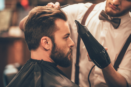 looking good: Looking good already. Close up side view of young bearded man getting groomed by hairdresser with hair dryer at barbershop