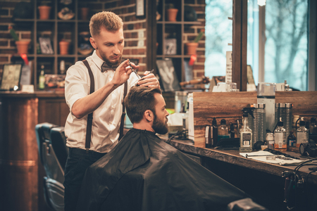 Making hair look magical. Young bearded man getting haircut by hairdresser while sitting in chair at barbershop Imagens
