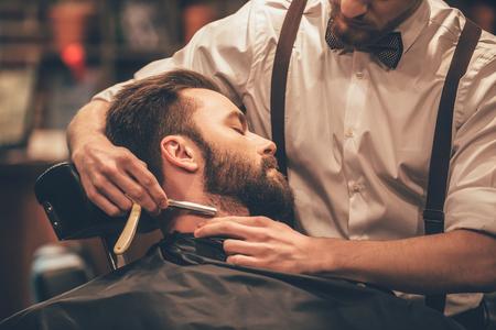hombres jovenes: Haciendo mirada del pelo m�gico. Primer plano vista lateral del hombre de la barba ni�o mientras se afeita con la maquinilla de afeitar borde recto por el peluquero en la peluquer�a