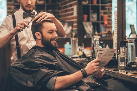 Geweldige tijd gehad in kapperszaak. Vrolijke jonge bebaarde man die kapsel krijgt door kapper en het lezen van de krant zittend in de stoel bij kapperszaak Stockfoto