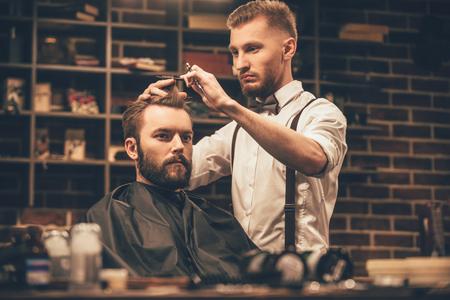 barbero: Hace corte de pelo un aspecto perfecto. hombre joven con barba que consigue corte de pelo de peluquería mientras está sentado en la silla en la peluquería