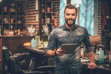 Mantener negocios en la parte superior con las tecnologías digitales. Hombre barbudo joven alegre que mira la cámara y la celebración de la tableta digital mientras está de pie en la barbería Foto de archivo