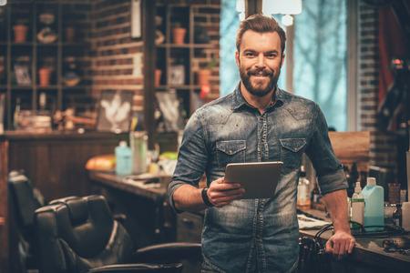 Manter negócios no topo com tecnologias digitais. homem de barba nova alegre que olha a câmera e que prende a tabuleta digital ao mesmo tempo em pé na barbearia