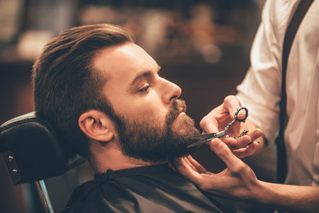 caucasian: Getting perfect shape. Close-up side view of young bearded man getting beard haircut by hairdresser at barbershop Stock Photo