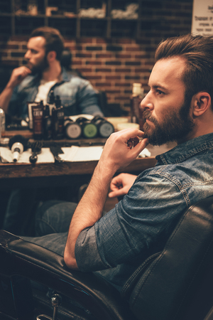 one man only: Looking awesome as ever. Side view of handsome young bearded man looking away and keeping hand on chin while sitting in chair at barbershop