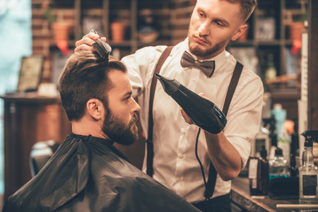 men hairstyle: New hairstyle. Side view of young bearded man getting groomed at hairdresser with hair dryer while sitting in chair at barbershop Stock Photo