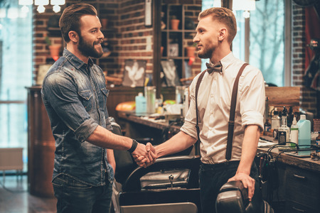 casual men: Thank you for quality haircut! Barber and his client shaking hands with smile while standing at barbershop