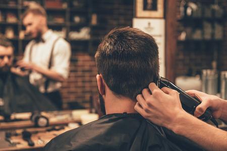guarnição nuca. Retrovisor do jovem homem recebendo corte de cabelo barba pelo cabeleireiro com lâmina elétrica ao sentar-se na cadeira na barbearia