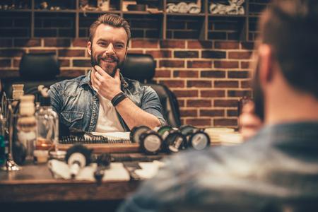 Apreciando a barba perfeita. homem barbudo jovem e bonito olhar para o seu reflexo no espelho e manter a m Imagens