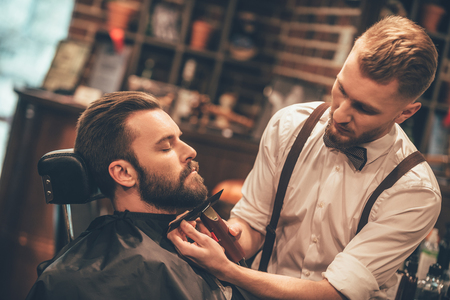 man with beard: Grooming of real man. Side view of young bearded man getting beard haircut at hairdresser while sitting in chair at barbershop Stock Photo