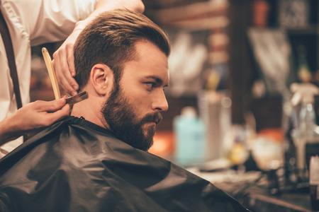Haciendo mirada del pelo mágico. Primer plano vista lateral de un joven con barba consigue corte de pelo con maquinilla de afeitar borde recto por el peluquero en la peluquería Foto de archivo