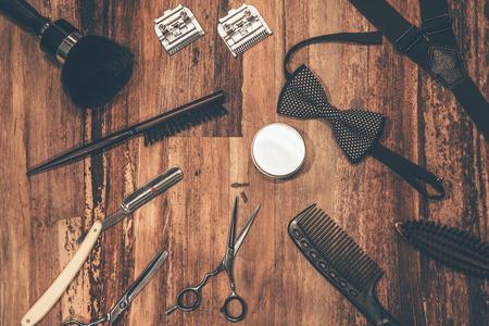 barbero: Herramientas del peluquero. Vista superior de herramientas de peluquería y accesorios hombres tumbado en la veta de la madera