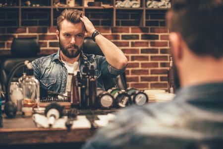 Tempo para novo corte de cabelo. homem barbudo jovem e bonito olhar para o seu reflexo no espelho e manter a mão no cabelo enquanto está sentado na cadeira em barbearia