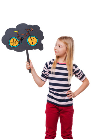 day dreaming: Dreaming about new bicycle. Girl holding thought bubble with drawn bicycle and looking at it while standing against white background Stock Photo