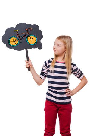 niños rubios: Sueño sobre nueva bicicleta. Muchacha que sostiene la burbuja de pensamiento con la bicicleta dibujada y mirarlo mientras está de pie contra el fondo blanco Foto de archivo