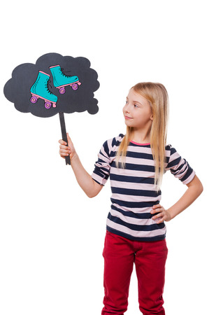 roller skates: Dreaming about new roller skates. Girl holding thought bubble with drawn roller skates and looking at it while standing against white background
