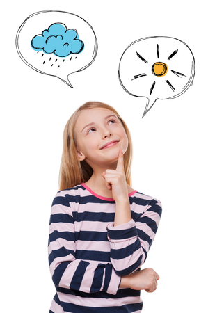hand on chin: Mood forecast. Cheerful girl holding hand on chin and looking at illustrated speech bubble while standing against white background Stock Photo