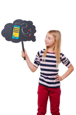 smart girl: Dreaming about new smart phone. Girl holding thought bubble with drawn smart phone and looking at it while standing against white background Stock Photo