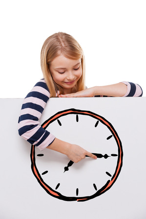 child hair: Time goes back. Cheerful girl leaning over white board with clock sketch on it and adjusting arrow while standing against white background
