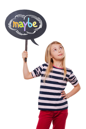 child looking up: Maybe... Thoughtful little girl holding speech bubble and looking up while standing against white background Stock Photo