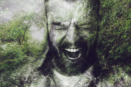 using voice: Furious man. Digitally composed image of furious young bearded man keeping mouth open and eyes closed over the picture of green forest