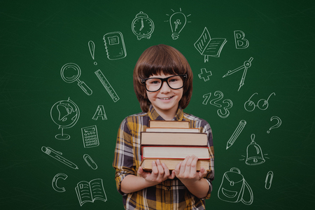 school children: Little genius. Cheerful boy holding books and looking at camera while standing against green blackboard with sketch on it Stock Photo
