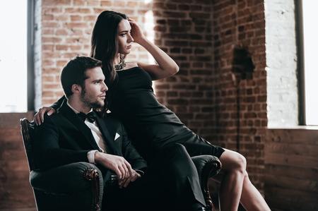 Pares elegantes. Hermosa joven pareja en ropa formal mirando a la ventana mientras se está sentado en una silla junto Foto de archivo