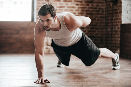 One hand push-up. Confident muscled young man wearing sport wear and doing one hand push-up while exercising on the floor in loft interior