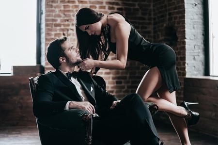 Tijd om te verleiden. Mooie jonge vrouw in cocktailkleding die aan haar vriendzitting leunen terwijl het bekijken elkaar in zolderbinnenland Stockfoto