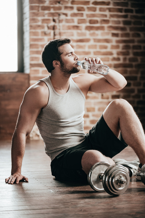 only the biceps: Honored sip. Confident muscled young man wearing sport wear and drinking water while sitting on the floor in loft interior