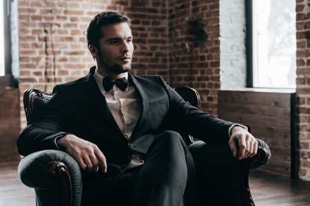 legs crossed on knee: Elegance is in his blood. Thoughtful young handsome man in formalwear and bow tie looking away while sitting in a chair in loft interior Stock Photo