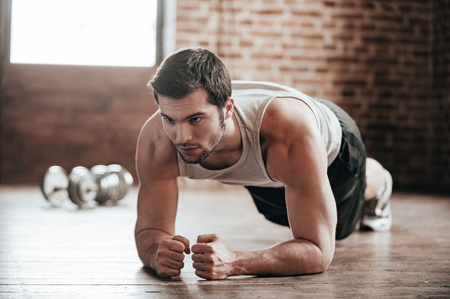 hombre deportista: Plank �l! joven musculoso seguro que lo lleva el desgaste del deporte y haciendo posici�n de tabla, mientras que ejercita en el suelo en el interior de loft