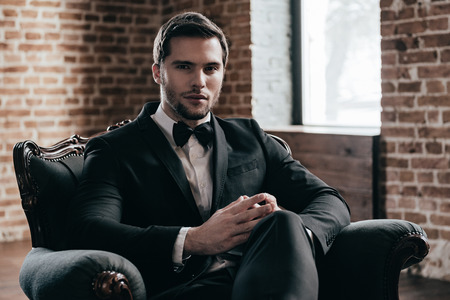 legs crossed at knee: Mr. Confidence. Young handsome man in formalwear and bow tie looking at camera while sitting in a chair in loft interior