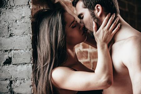 sexo pareja joven: Solo un beso. Vista lateral de la joven y bella besar par de amante mientras est� de pie cerca de la pared de ladrillo
