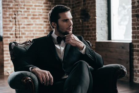 one adult only: Royalty in his blood. Thoughtful young handsome man in formalwear and bow tie looking away and holding hand on chin while sitting in a chair in loft interior