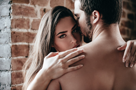 beautiful naked woman: Feeling calm and protected. Close-up of beautiful young shirtless couple hugging while woman looking over shoulder of her boyfriend