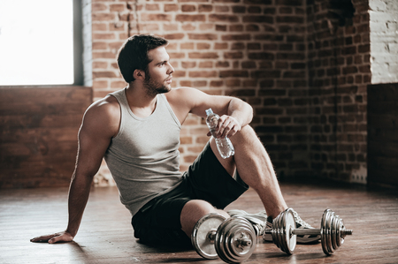 muscle guy: Resting time. Confident muscled young man wearing sport wear and sitting on the floor with bottle of water in loft interior Stock Photo