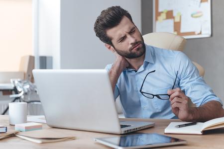 Sich erschöpft fühlen. Frustrierte junge gut aussehend Mann auf der Suche erschöpft, während an seinem Arbeitsplatz sitzt und seine Brille in der Hand trägt,