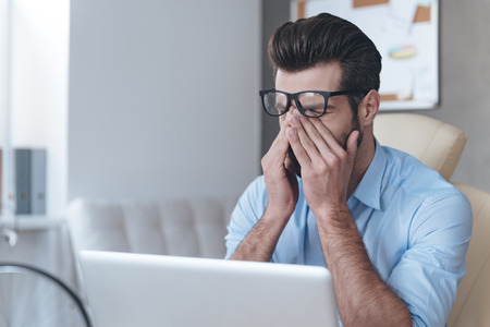 headache pain: Feeling tired. Frustrated young handsome man looking exhausted and covering his face with hands while sitting at his working place  Stock Photo