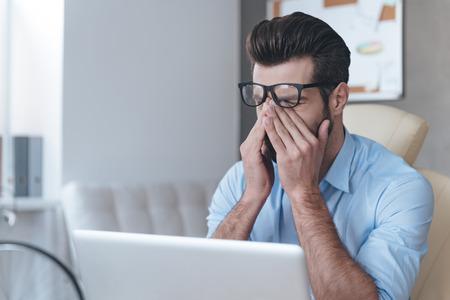 inteligencia: Sensaci�n de cansancio. joven apuesto hombre frustrado que mira agotado y cubri�ndose la cara con las manos mientras est� sentado en su lugar de trabajo Foto de archivo
