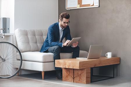EMPRESARIO: La multitarea. joven hombre que usaba gafas y el trabajo con pantalla táctil mientras se está sentado en el sofá en la oficina