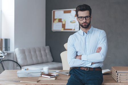 office man:  Perfect manager. Handsome young man wearing glasses looking at camera and keeping arms crossed while standing in office