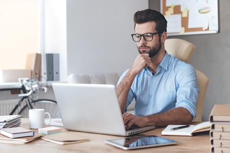 Ocupado trabajando. jóvenes gafas que desgastan del hombre guapo pensativo que trabaja en la computadora portátil y el mantenimiento de la mano en la barbilla mientras se está sentado en su lugar de trabajo