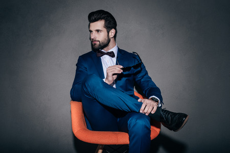legs crossed on knee: Stylish as ever. Young handsome man in suit holding his sunglasses and looking away while sitting in orange chair against grey background Stock Photo